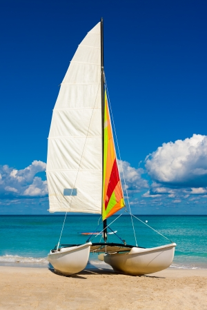 Catamaran with its colorful sail spread out on Varadero beach in Cuba photo