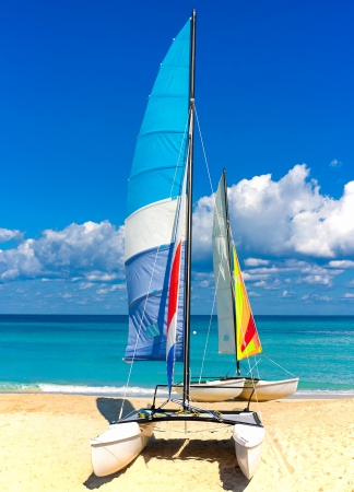 Two colorful catamarans with their sails spread out the cuban beach of Varadero photo