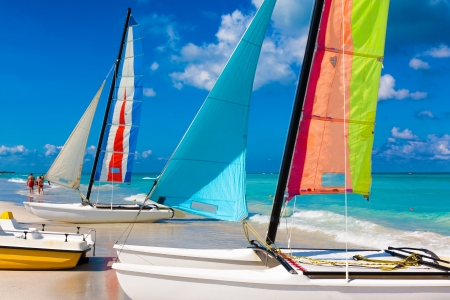 Sailing boats with its colorful sails spread out on Varadero beach in Cuba photo