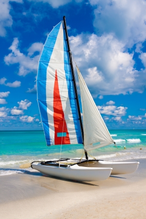 Sailing boat with its colorful sail spread out on Varadero beach in Cuba photo