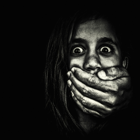 Horror portrait of a very frightened girl with an adult hand covering her mouth isolated on a white background photo