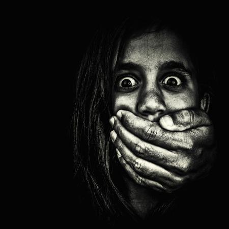 detenuti: Horror ritratto di una ragazza molto spaventata, con mano di un adulto copre la bocca isolato su uno sfondo bianco Archivio Fotografico