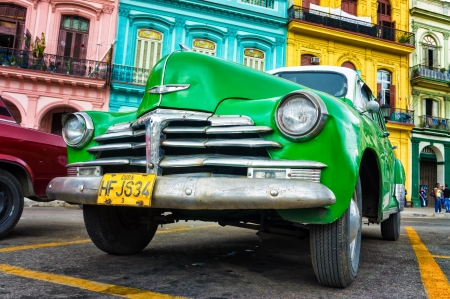 Old Chevrolet in front of colorful buildings  in Havana Thousands of these cars are still in use in Cuba and they have become an iconic view of the cuban cities