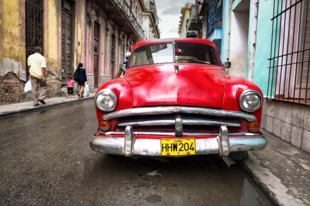 Old classic car in a shabby neighborhood  in Havana Thousands of these vintage cars are still in use in Cuba and they have become an iconic view of the cuban cities