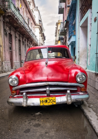 Old classic car in a shabby neighborhood  in Havana Thousands of these vintage cars are still in use in Cuba and they have become an iconic view of the cuban cities Stock Photo - 16605972