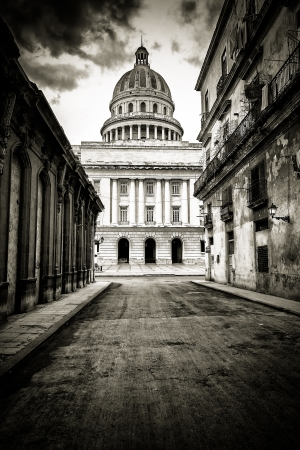 crumbling: Grungy black and white image of a street with crumbling buildings leading to the Capitol in Old Havana Stock Photo