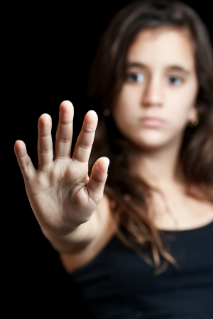 negation: Hispanic girl with her hand extended signaling to stop useful to campaign against violence, gender or sexual discrimination  Focused on her hand