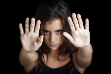 violencia sexual: Ni�a hispana con la mano extendida de se�alizaci�n para detener �til para hacer campa�a contra la violencia, el sexo o la discriminaci�n sexual Centrado en la mano Foto de archivo