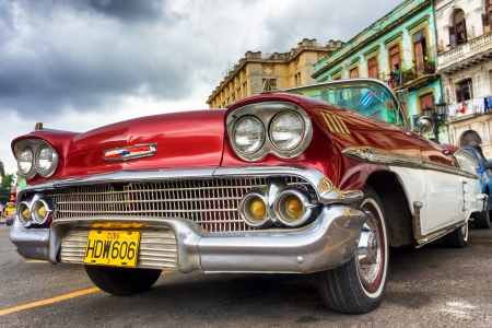 car grill: Old red Chevrolet near the Capitol  in Havana Thousands of these cars are still in use in Cuba and they have become an iconic view and a worldwide known attraction