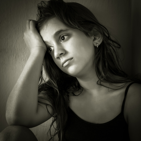 Monochromatic portrait of a sad hispanic girl sitting in a corner with a dirty wall background photo