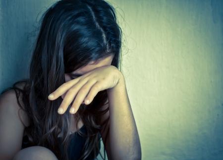 verdrietig meisje: Verdrietig en eenzaam meisje huilen met een hand die haar gezicht met ruimte voor tekst Stockfoto