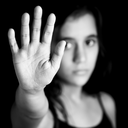 discrimination: Black and white image of a girl with her hand extended signaling to stop useful to campaign against violence, gender or sexual discrimination  image focused on her hands  Stock Photo