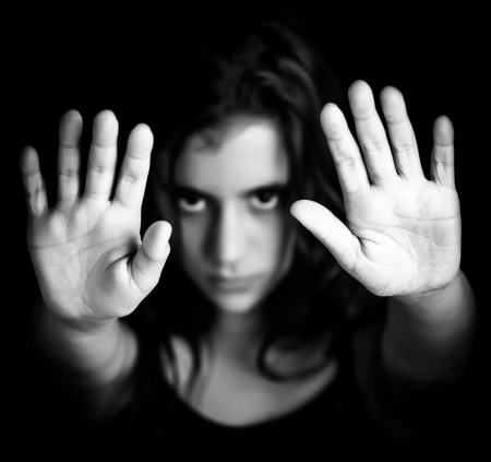 Black and white image of a girl with her hand extended signaling to stop useful to campaign against violence, gender or sexual discrimination  image focused on her hands  Stock Photo