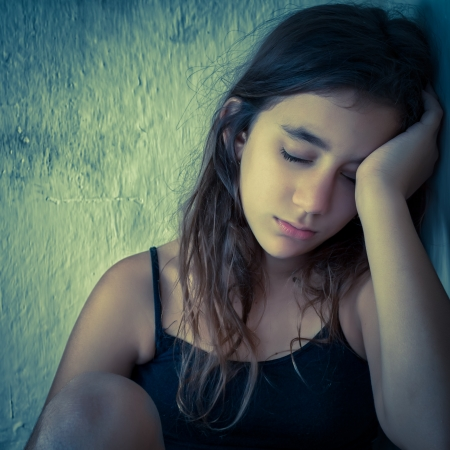 Sad and tired hispanic girl sitting next to a dirty wall toned in blue shades Stock Photo - 16733830
