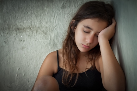 Tired and lonely hispanic girl sitting next to a dirty wall with her eyes closed photo
