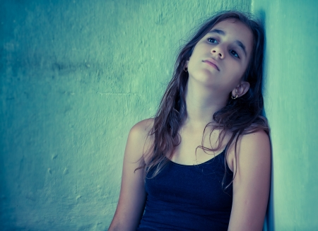abused women: Artistic portrait of a sad hispanic girl sitting next to a dirty wall toned in blue shades Stock Photo