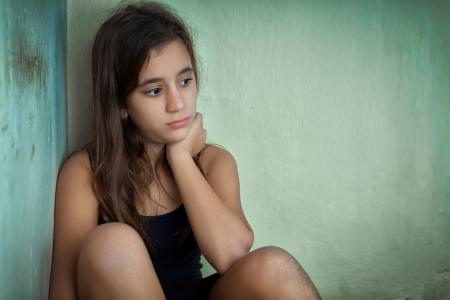 fille triste: Triste et solitaire fille hispanique assis dans le coin d'une maison grungy