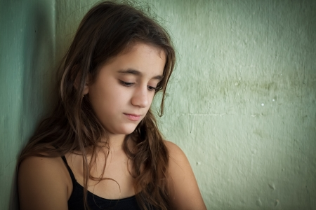 long depression: Depressed girl with a sad expression leaning on a dirty old wall Stock Photo