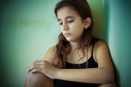 arme kinder: Einsame hispanische Mädchen mit einem sehr traurigen Ausdruck sitzt auf einer Ecke