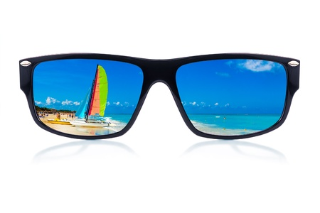 Modern sunglasses with a tropical beach reflection isolated on a white background