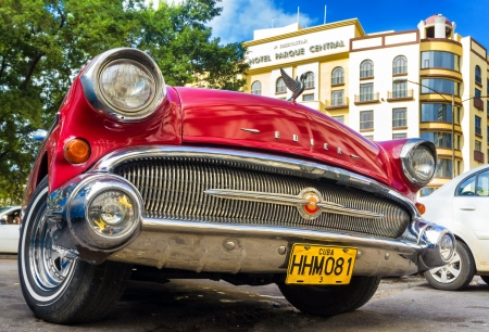 car grill: Shiny red 1957 Buick waiting for tourists near a hotel  in Havana