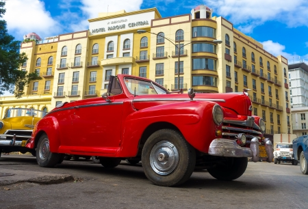 Vintage red Ford parked in front of the Central Park hotel  in Havana