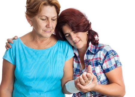 caring for: Young hispanic woman caring for an alderly lady with a broken arm  isolated on white