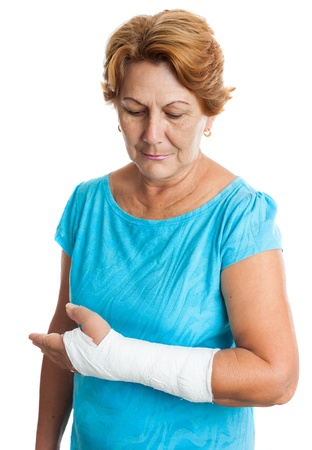 bone fracture: Senior hispanic woman with a broken arm on a plaster cast  isolated on white  Stock Photo