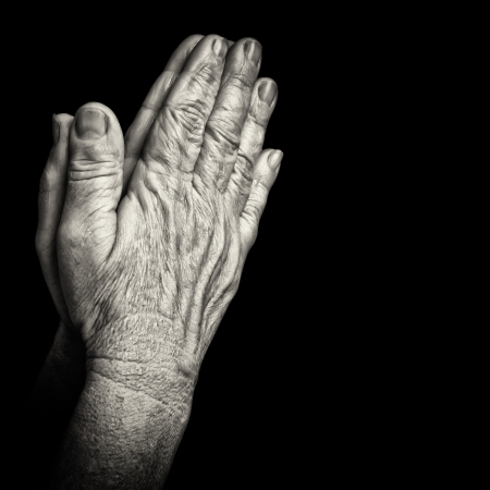 Black and white portrait of old wrinkled hands praying isolated on black with space for text
