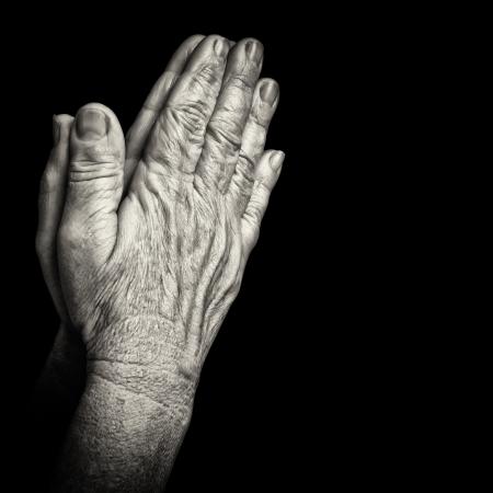 manos orando: Retrato en blanco y negro de las viejas arrugadas manos rezando aislado en negro con el espacio para el texto Foto de archivo