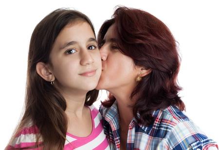madre con hija: Madre hispana besando a su hija hermosa aislado en blanco Foto de archivo