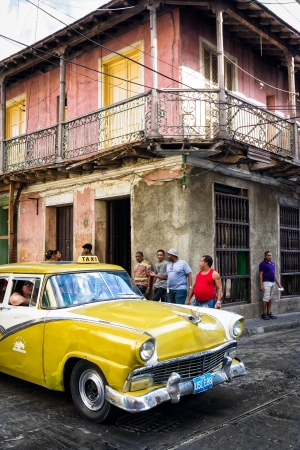 SANTIAGO DE CUBA,CUBA-JANUARY 11 Old Buick next to crumbling buildings January 11,2013 in Santiago de Cuba Thousands of these classic cars are used as taxis and private vehicles across the country