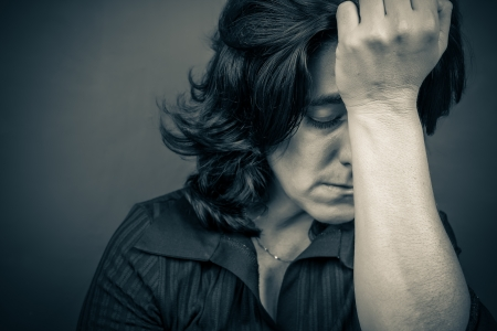 worried woman: Dramatic  blue toned portrait of a woman suffering a headache or a strong depression