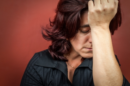 Dramatic  portrait of a woman suffering a headache or a strong depression with a dark red background photo