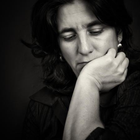 Dramatic black and white portrait of sad and thoughtful woman photo