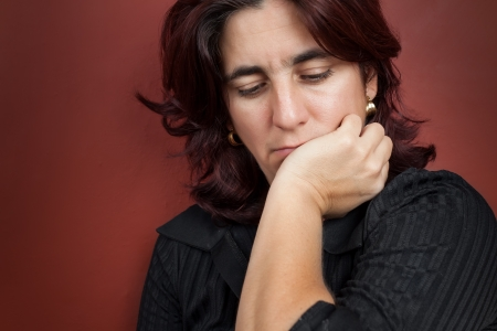 depressed woman: Portrait of a worried and thoughtful  woman with a dark red background Stock Photo