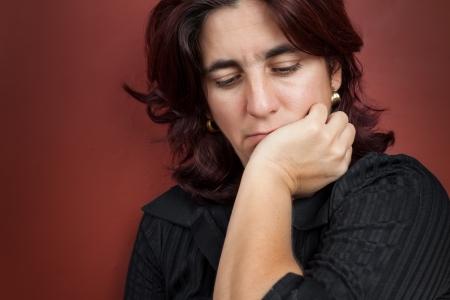 ragazza depressa: Ritratto di una donna preoccupata e premurosa con uno sfondo rosso scuro