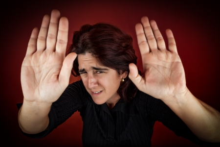 abused: Frightened woman defending herself against an imminent aggression Stock Photo