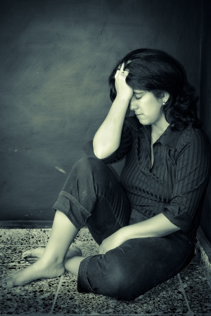 Grunge portrait of a very depressed woman sitting on the floor photo