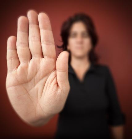 conflictos sociales: Mujer con la mano extendida de se�alizaci�n para detener s�lo la mano est� enfocado sobre un fondo rojo