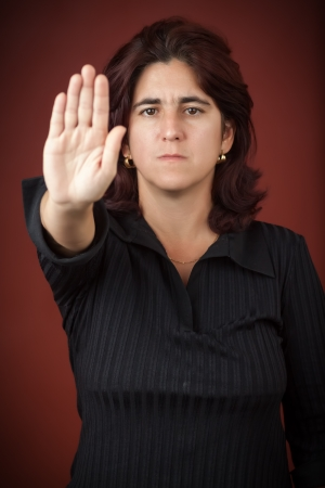 Serious hispanic woman with her hand extended signaling to stop  useful to campaign against violence or discrimination  photo
