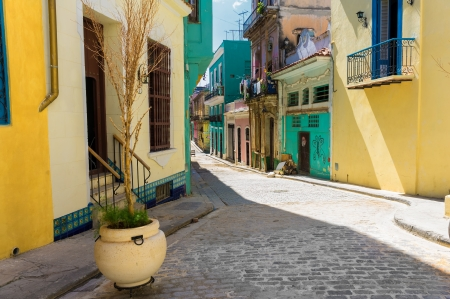 narrow: Narrow street sidelined by colorful buildings in Old Havana Stock Photo