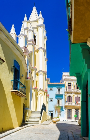 Colorful street in Old Havana with the Church of the Angel, a historical and religious landmark, on a beautiful day with a clear blue sky Stock Photo - 18268123