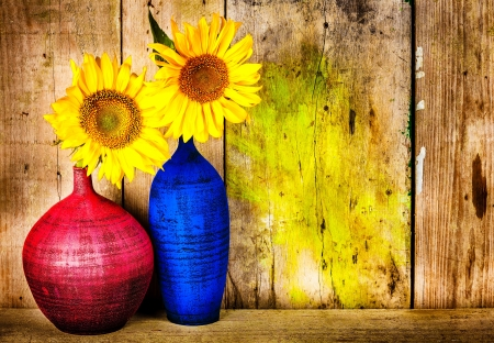 Colorful vases with bright yellow sunflowers on an old wooden background photo