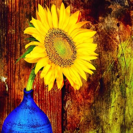Zonnebloem op een blauwe vaas met een grunge rustieke houten achtergrond