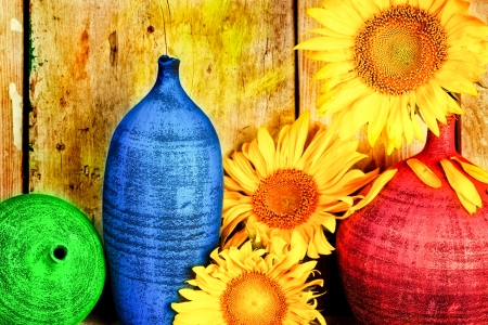 Vintage image of sunflowers and pottery with  a rustic wood planks background photo