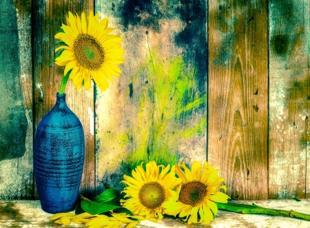 Beautiful vintage image of sunflowers and pottery vases with a grunge wooden planks background photo