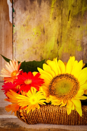 Basket with sunflowers and daisies on a vintage wooden background photo