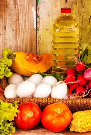 Assorted vegetables , eggs and a bottle of oil on a basket with a rustic wooden background photo