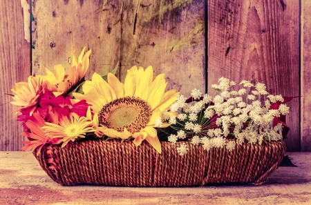 Vintage image of flowers on a basket with a rustic wooden background photo
